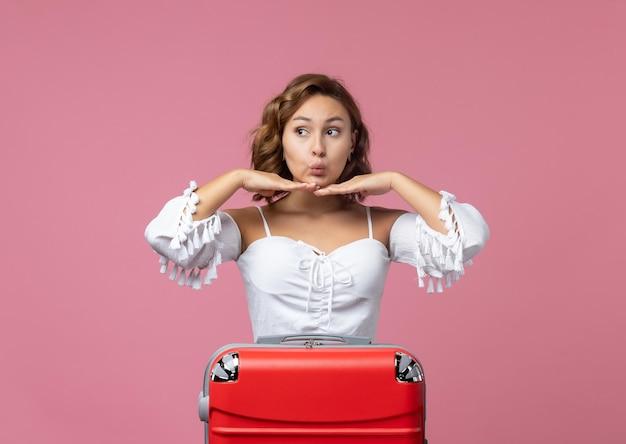 Vue de face d'une jeune femme posant avec son sac rouge sur le mur rose