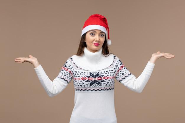 Vue de face jeune femme avec pose confuse sur fond marron émotion noël nouvel an