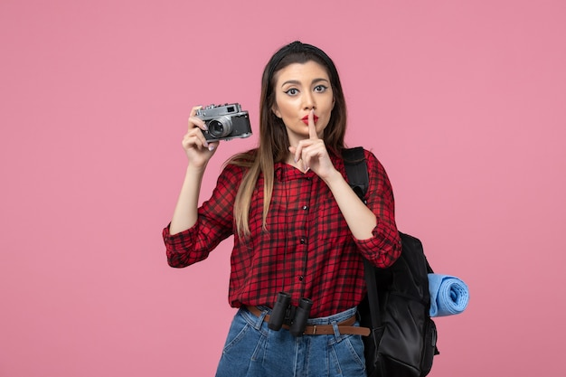 Vue de face jeune femme prenant photo avec appareil photo sur fond rose femme photo couleur