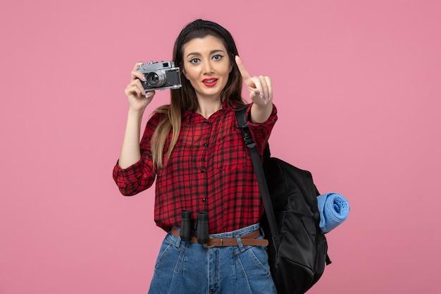 Vue de face jeune femme prenant photo avec appareil photo sur fond rose photo couleur femme