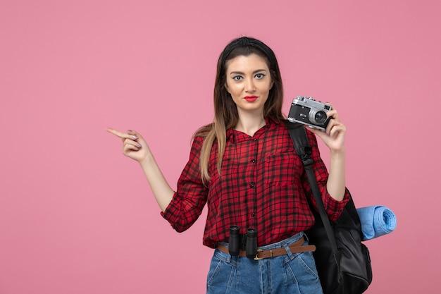 Vue de face jeune femme prenant photo avec appareil photo sur un modèle photo femme fond rose