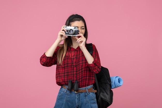Vue de face jeune femme prenant une photo sur fond rose couleur femme humaine