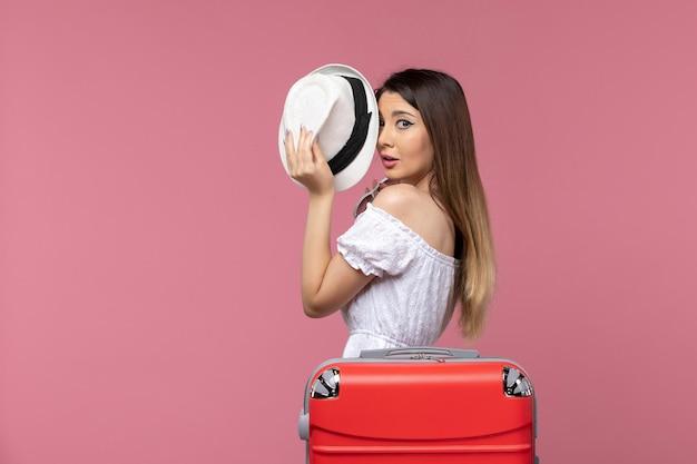 Vue de face jeune femme prépare pour des vacances sur fond rose clair voyage voyage voyage à l'étranger voyage mer