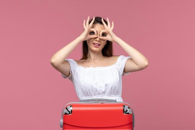 Vue de face jeune femme prépare pour des vacances sur fond rose à l'étranger voyage voyage en mer voyage voyage