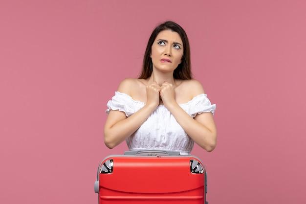 Vue de face jeune femme prépare pour des vacances sur fond rose vacances à l'étranger voyage voyage voyage