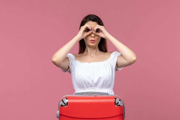 Vue de face jeune femme prépare pour des vacances sur fond rose vacances voyage voyage voyage à l'étranger