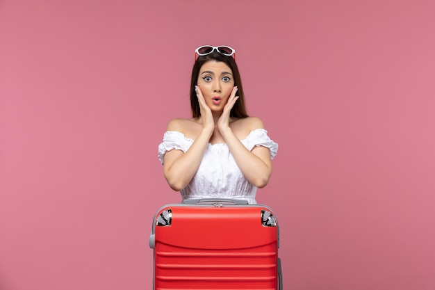 Vue de face jeune femme prépare pour des vacances sur le fond rose voyage voyage voyage femme mer à l'étranger