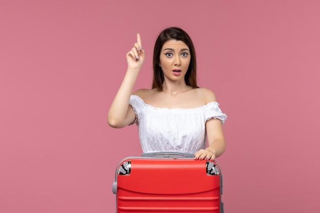 Vue de face jeune femme prépare pour les vacances avec son gros sac sur fond rose à l'étranger voyage en mer voyage voyage voyage