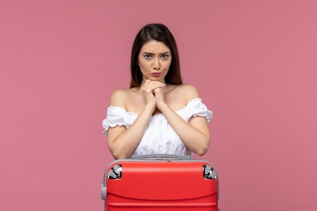 Vue de face jeune femme prépare pour les vacances avec son sac sur le bureau rose à l'étranger voyage en mer voyage voyage voyage