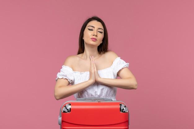 Vue de face jeune femme prépare pour les vacances avec son sac sur le fond rose à l'étranger voyage en mer voyage voyage voyage