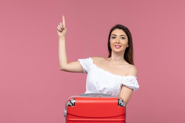 Vue de face jeune femme prépare pour les vacances avec son sac rouge sur le fond rose voyage à l'étranger voyage voyage en mer