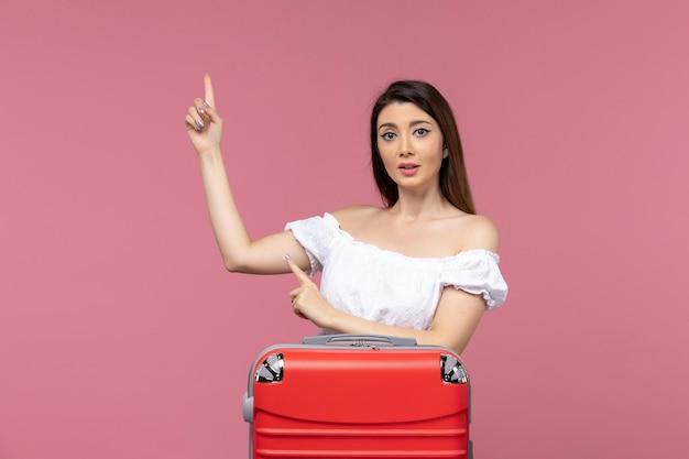 Vue de face jeune femme prépare pour les vacances avec son sac rouge sur fond rose voyage voyage à l'étranger voyage voyage