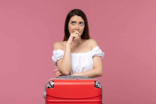 Vue de face jeune femme prépare pour les vacances avec son sac sur le sol rose à l'étranger voyage en mer voyage voyage voyage