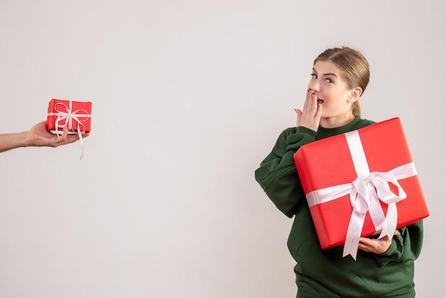 Vue de face jeune femme avec présent et acceptant le petit cadeau de l'homme