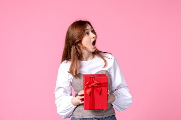 Vue de face jeune femme avec présent dans un emballage rouge sur fond rose mars cadeau sensuel horizontal de l'égalité de l'argent photo parfum