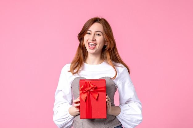 Vue de face jeune femme avec présent dans un emballage rouge sur fond rose mars cadeau sensuel horizontal femme de l'égalité de l'argent de photo de parfum de cadeau