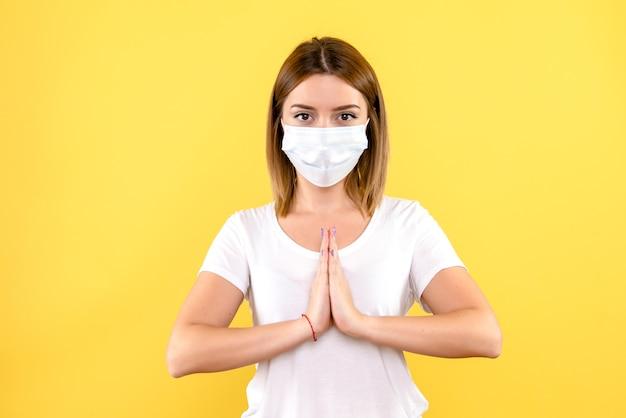 Vue de face de la jeune femme priant en masque sur mur jaune