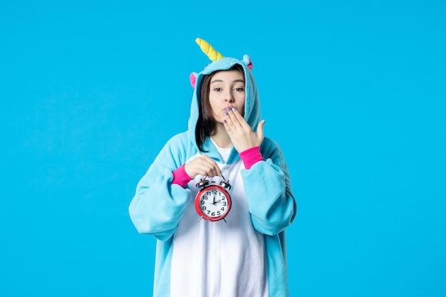 Vue de face jeune femme en pyjama party holding horloges sur fond bleu fin de rêve lit cauchemar fun nuit de sommeil temps de jeu femme