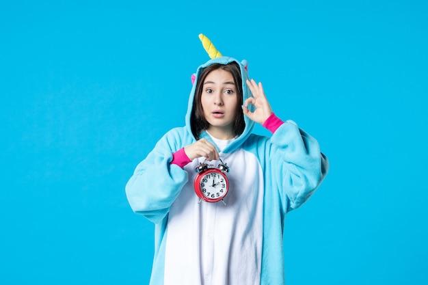 Vue de face jeune femme en pyjama party holding horloges sur fond bleu lit de rêve tard cauchemar fun sommeil nuit repos temps de jeu femme