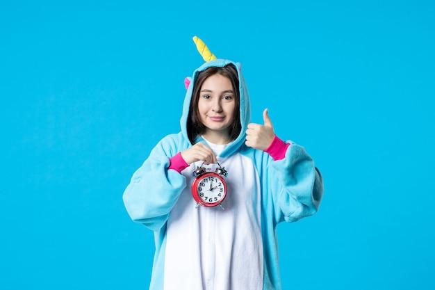 Vue de face jeune femme en pyjama party holding horloges sur fond bleu lit de rêve tard cauchemar fun sommeil repos temps de jeu femme