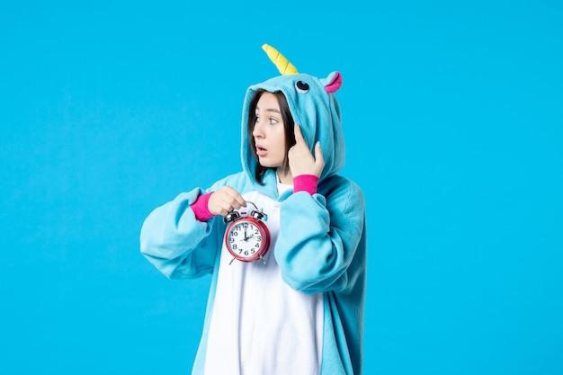 Vue de face jeune femme en pyjama party holding horloges sur fond bleu lit de rêve tardif femme cauchemar fun nuit de sommeil temps de jeu