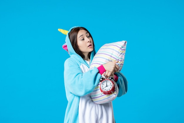 Vue de face jeune femme en pyjama party avec horloges et oreiller sur fond bleu lit de rêve sommeil tard cauchemar nuit amis bâillement