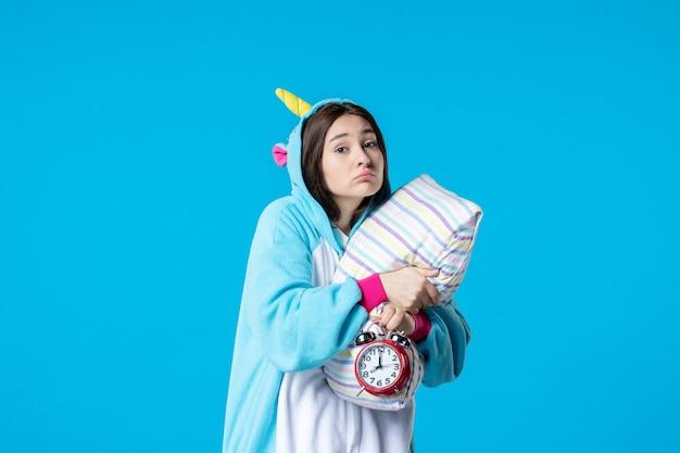 Vue de face jeune femme en pyjama party avec horloges et oreiller sur fond bleu lit de rêve sommeil tard repos cauchemar nuit amis bâillement