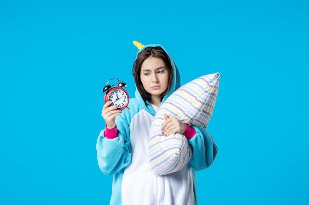 Vue de face jeune femme en pyjama party avec horloges et oreiller sur fond bleu lit de rêve sommeil tard repos nuit amis bâillement