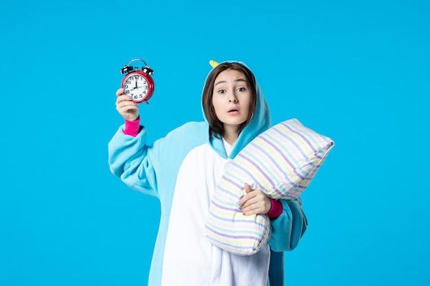 Vue de face jeune femme en pyjama party avec horloges et oreiller sur fond bleu lit de rêve sommeil tard reste cauchemar amis bâillement
