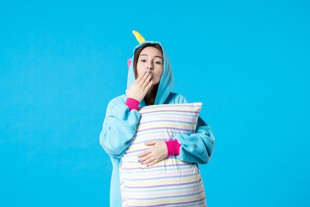 Vue de face jeune femme en pyjama pour une fête de pyjama tenant un oreiller sur fond bleu lit nuit repos sommeil cauchemar femme en retard rêves amusants jeu de baiser