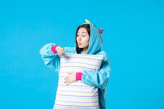 Vue de face jeune femme en pyjama pour pyjama party holding oreiller sur fond bleu lit femme nuit repos cauchemar fin fun rêves jeu sommeil