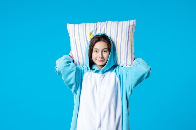 Vue de face jeune femme en pyjama pour pyjama party holding oreiller sur fond bleu lit femme nuit repos fin fun rêves jeu sommeil cauchemar