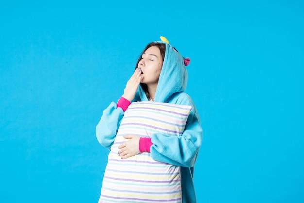 Vue de face jeune femme en pyjama pour pyjama party holding oreiller sur fond bleu lit femme nuit repos sommeil cauchemar fin fun rêves jeu