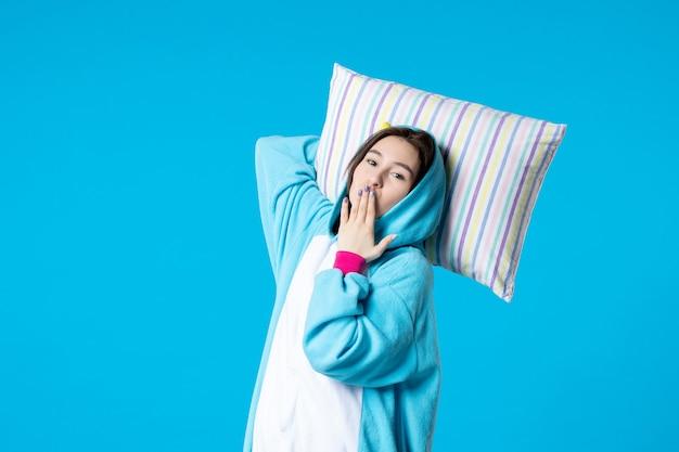 Vue de face jeune femme en pyjama pour pyjama party holding oreiller sur fond bleu lit femme reste tard fun rêves jeu sommeil cauchemar nuit