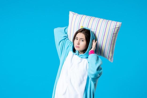 Vue de face jeune femme en pyjama pour pyjama party holding oreiller sur fond bleu tard lit femme reste fun rêves jeu sommeil cauchemar nuit