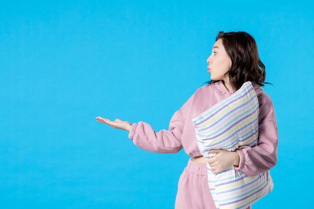 Vue de face jeune femme en pyjama rose avec oreiller sur le lit de couleur bleu nuit reste rêve femme insomnie