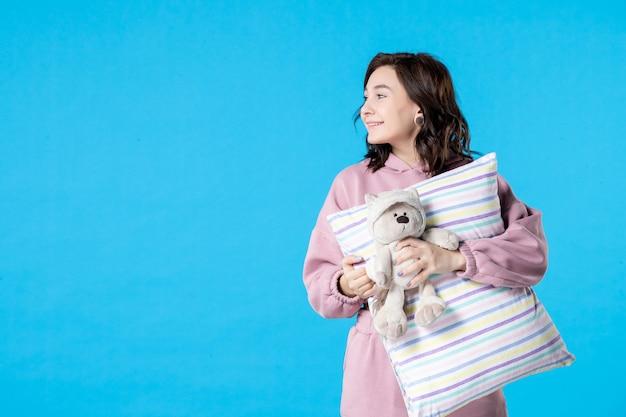 Vue de face jeune femme en pyjama rose parlant à quelqu'un sur le lit bleu insomnie nuit cauchemar repos sommeil