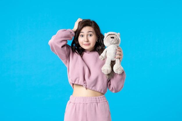 Vue de face jeune femme en pyjama rose avec petit ours en peluche sur couleur de rêve bleu nuit sommeil insomnie repos fête de lit