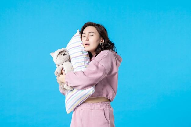 Vue de face jeune femme en pyjama rose avec petit ours en peluche et oreiller sur lit bleu nuit cauchemar sommeil femme reste insomnie fête de rêve