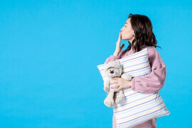 Vue de face jeune femme en pyjama rose avec petit ours en peluche et oreiller sur lit d'insomnie bleu nuit cauchemar fête reste sommeil