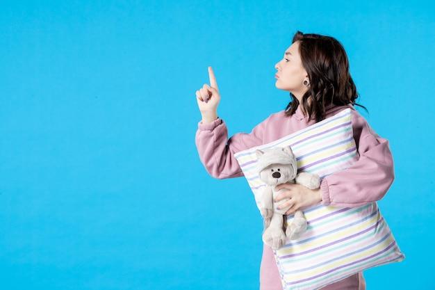 Vue de face jeune femme en pyjama rose avec petit ours en peluche et oreiller sur lit d'insomnie bleu nuit fête de rêve reste sommeil
