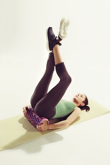 Vue de face d'une jeune femme qui s'étend du corps en classe de gymnastique.