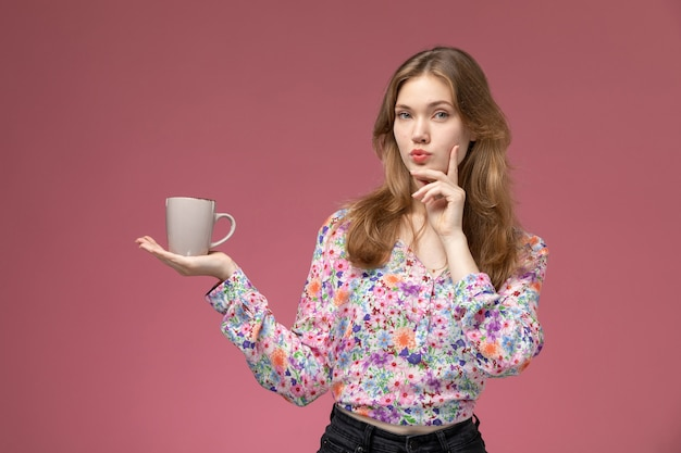 Vue de face jeune femme réfléchissant à quelque chose de grand avec holding cup