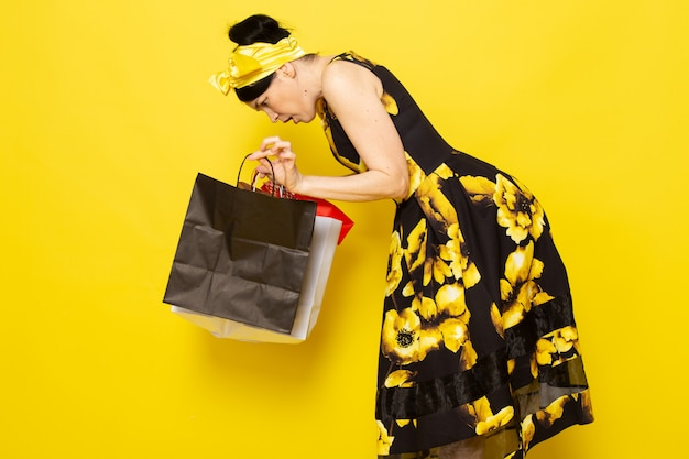 Une vue de face jeune femme en robe de fleur jaune-noir conçu avec un bandage jaune sur la tête mécontent de la tenue de colis sur le jaune