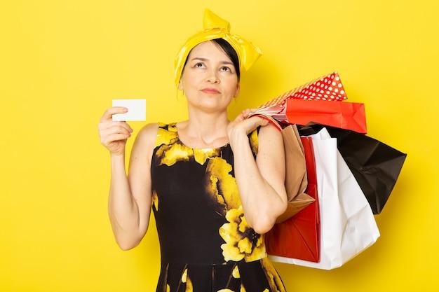 Une vue de face jeune femme en robe de fleur jaune-noir conçu avec un bandage jaune sur la tête tenant des colis sur le jaune
