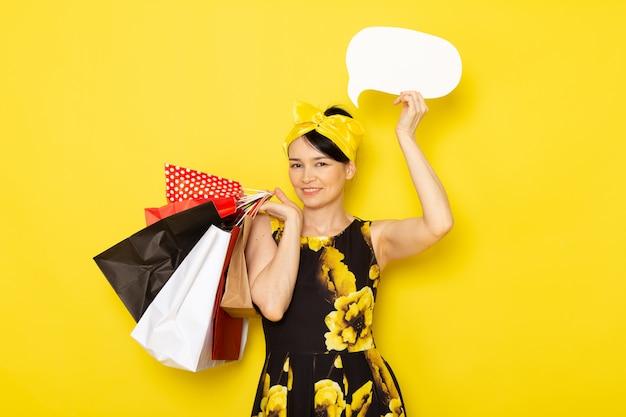 Une vue de face jeune femme en robe de fleur jaune-noir conçu avec un bandage jaune sur la tête tenant des paquets commerciaux panneau blanc sur le jaune