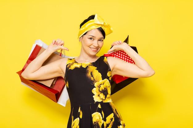 Une vue de face jeune femme en robe de fleur jaune-noir conçu avec un bandage jaune sur la tête tenant des paquets shopping souriant sur le jaune