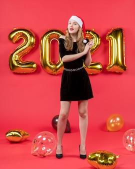 Vue de face jeune femme en robe noire ballons sur rouge
