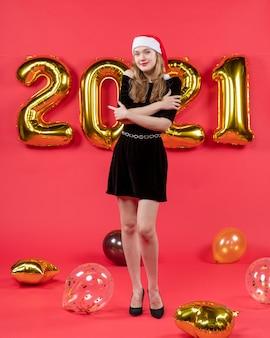 Vue de face jeune femme en robe noire croisant ses mains ballons sur rouge