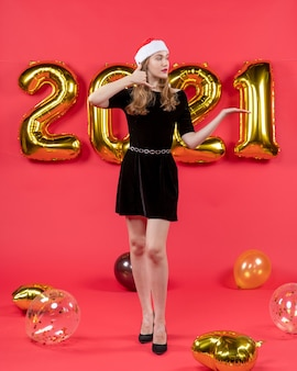 Vue de face jeune femme en robe noire faisant m'appeler signe des ballons sur rouge
